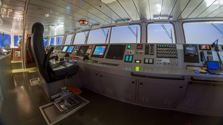 The bridge of a modern cargo ship with various electronic inputs